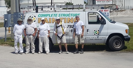a picture of our licensed painters standing next to one of our trucks